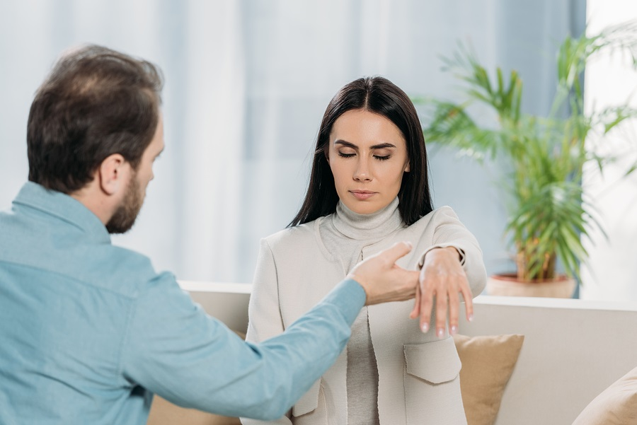 bearded hypnotist holding wrist of young woman with closed eyes during hypnotherapy